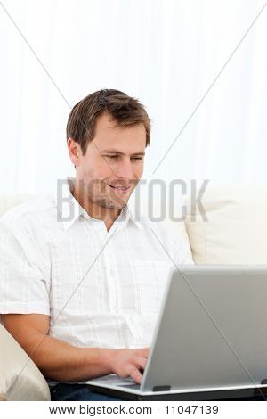 Happy Man Working On His Laptop On The Sofa