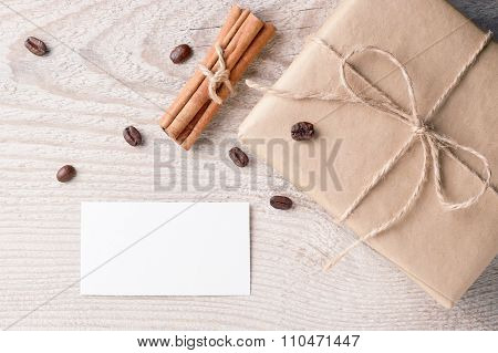 Gift box with blank card nearby decorated scattered coffee beans and cinnamon on old white wooden ta