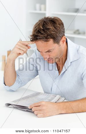 Concentrated Man Doing A Cryptic Crossword Sitting In His Kitchen