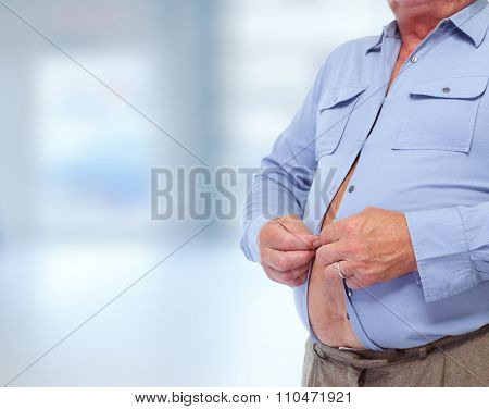 Senior man with big fat stomach over blue background. Obesity concept.