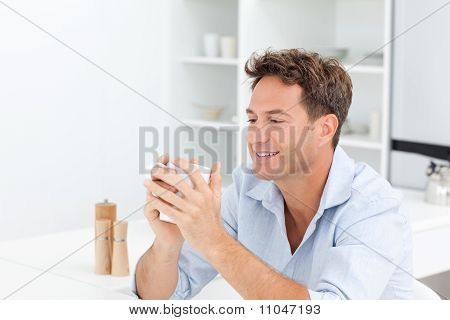 Attractive Man Drinking Coffee Sitting At A Table