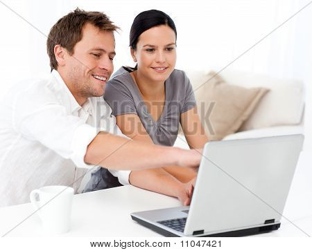 Cute Man Showing Something On The Laptop Screen To His Girlfriend