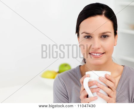 Lovely Woman Holding A Cup Of Coffee While Relaxing In The Kitchen