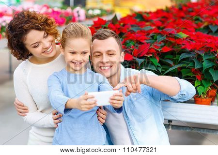 Young family taking selfies in the greenhouse