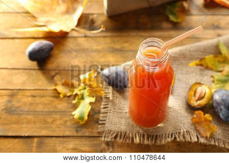 Plum Juice in a glass bottle with fresh fruits