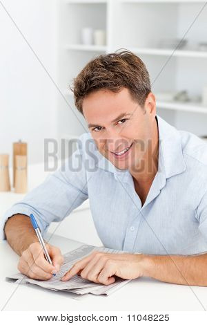 Smart Man Doing A Cryptic Crossword Sitting In His Kitchen