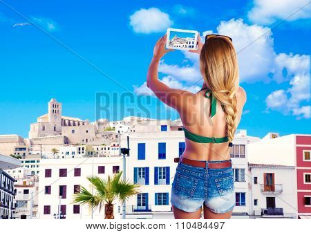 Blond tourist girl taking photos of Ibiza skyline photomount