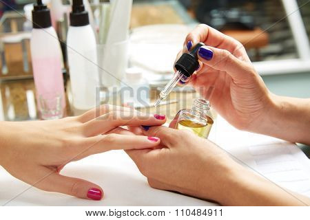 Nails top coat finishing vernis after nail polish in woman hands at salon