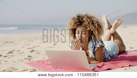 Young african american woman smiling while surfing the net at beach.