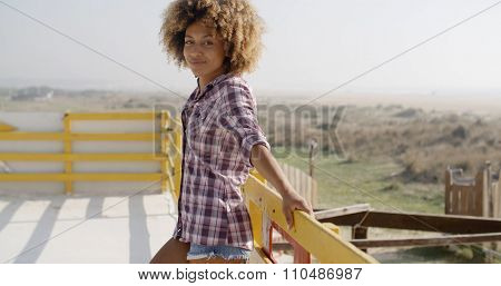 Close up portrait of a happy african american woman smiling outdoors with hand up
