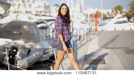 Young woman Goes Ashore From A Boat and walking on dock near the boats