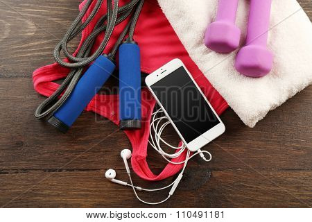 Smart phone, sport clothes and equipment on wooden background