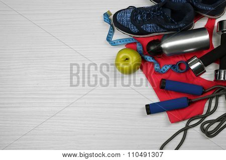 Sport clothes, shoes and sport equipment on light background