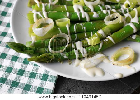 Fresh asparagus dish with sliced onion on white plate with checkered cotton serviette on grey table, close up