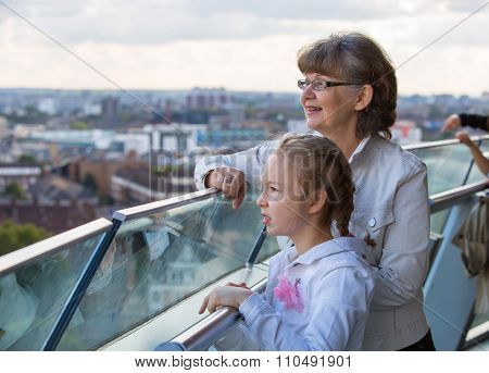 Elderly woman and granddaughter enjoying the London view. Background includes modern building City o