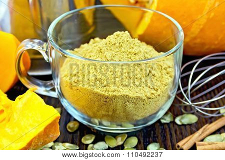 Flour pumpkin in glass cup with seeds and a mixer on board