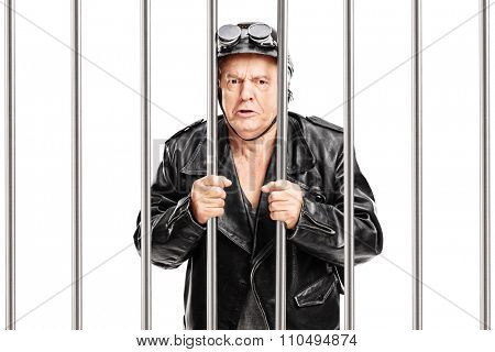 Arrested senior motorcyclist in a black leather jacket standing in jail and looking at the camera isolated on white background