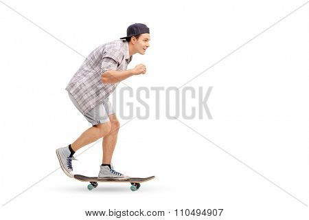 Full length profile shot of a young man riding a skateboard and smiling isolated on white background