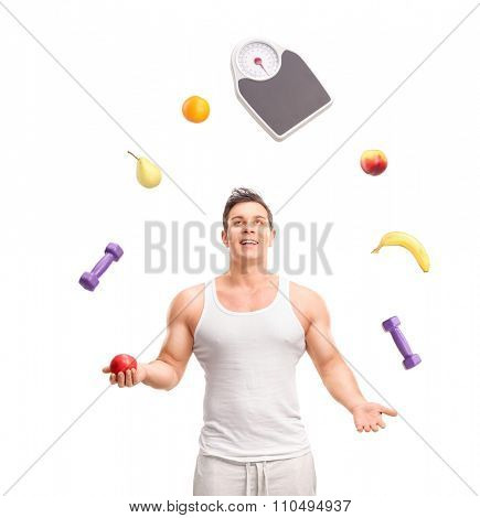 Handsome young guy juggling with several fruits and a weight scale isolated on white background