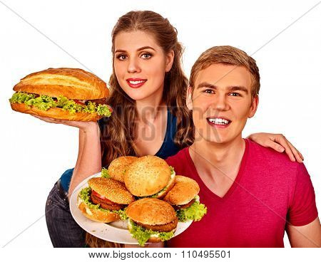 Young couple man and woman holding a lot of hamburgers  . Fastfood concept.  Isolated.