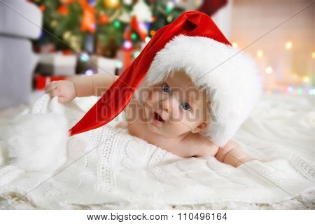 Naked baby in red hat on the floor in the decorated Christmas room