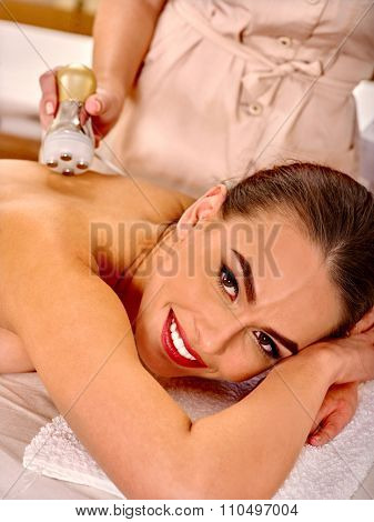 Beautiful woman receiving electroporation back therapy at beauty salon.