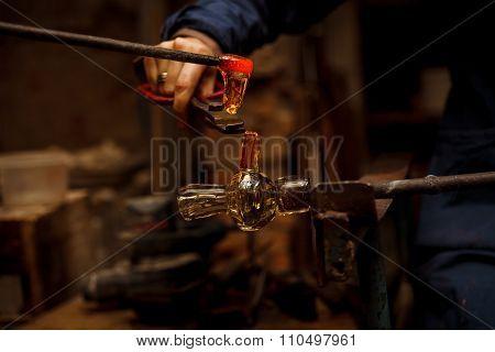 Glass Artist in her workshop making glassware