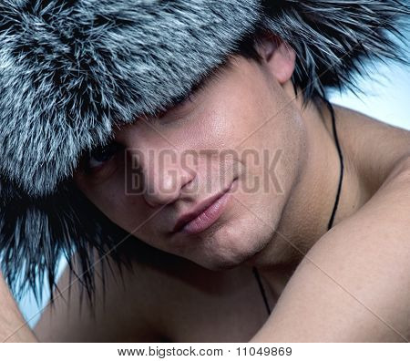 Portrait of handsome young man wearing fluffy hat
