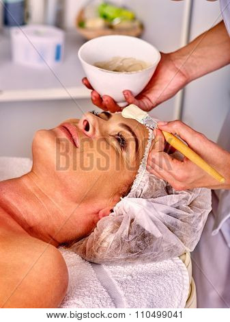 Woman middle-aged in hat take facial and neck clay mask in spa salon.