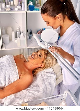 Woman middle-aged lying in spa salon with cosmetic lamp . The background shelves cosmetics.