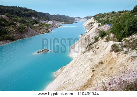 Turquoise chalk quarry in the forest in Belarus