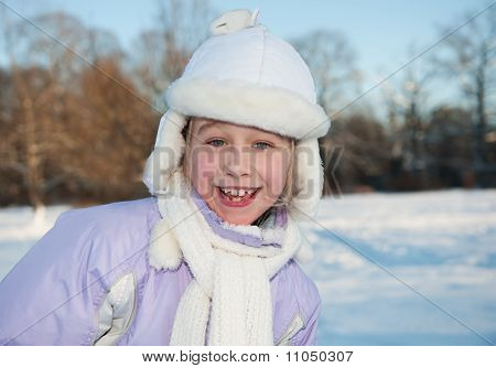 Happy young girl in white hat winter portrait