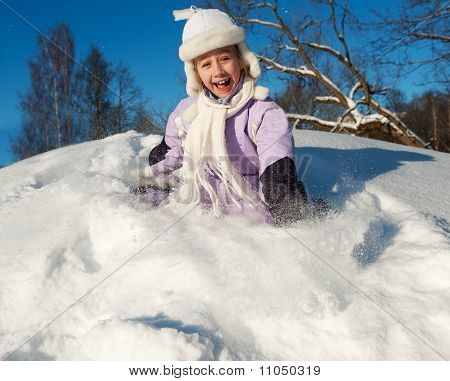 Funny little girl sliding in the snow