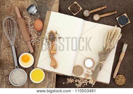 Baking ingredients and kitchen equipment on hemp notebook, old wooden board and lokta background.