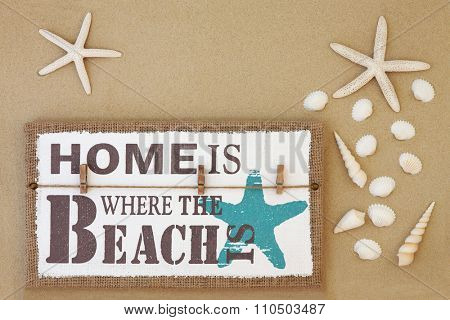 Home is where the beach is distressed wooden sign with starfish and shell selection on sand background.