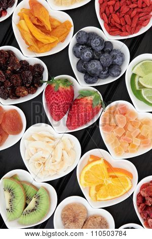Healthy superfood fruit selection in heart shaped porcelain dishes over wooden black background, high in vitamins and antioxidants.