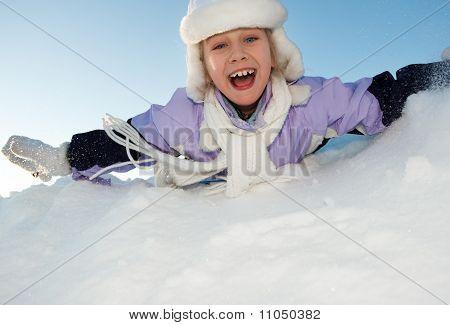 Funny little girl deslizante en la nieve