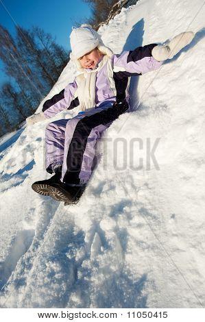 Little girl sliding in the snow