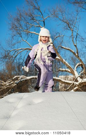 Funny little girl running in the snow