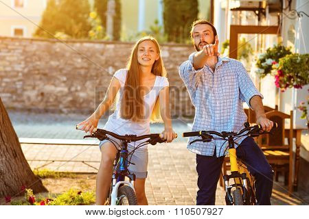 happy young couple of bicyclists talking in the street