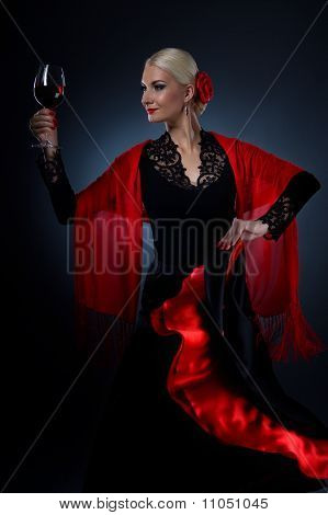 Beautiful flamenco dancer holding a glass of wine