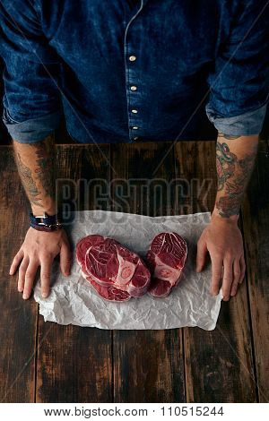 Top View Of Butcher's Tattoed Hands And Steaks On Craft Paper