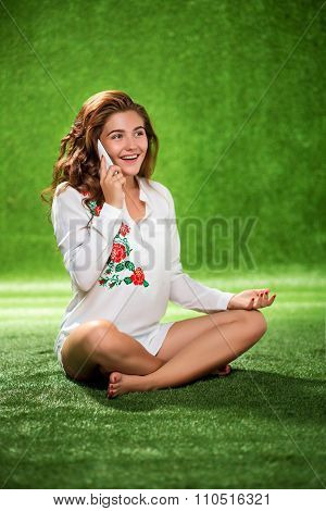 Pretty girl sitting on the grass talking phone, young attractive