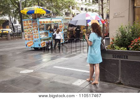 new york city, USA, 11 september 2015: woman with umbrella looks at Hotdog Vendor On Corner Of Water
