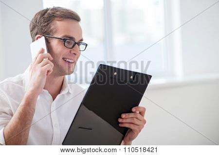 Handsome young businessman is communicating on telephone