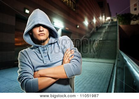 Young handsome man in a hood outdoors