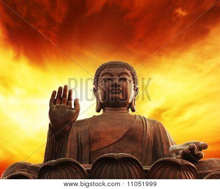 Statue of Buddha over yellow sky