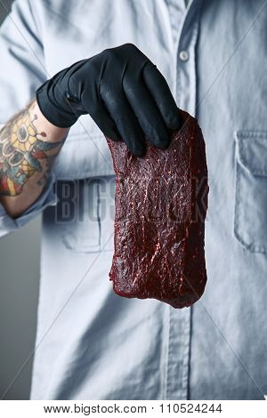 Tattoed Hand In Black Glove Holds Piece Of Luxury Steak In Air