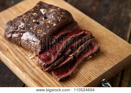 Closeup Of Sliced Medium Rare Cooked Whale Meat Stake Wooden Table