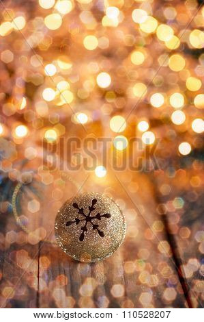 Gold Metal Jingle Bell With Snowflake On Wooden Table With Boke